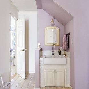 Immagine di un bagno di servizio tradizionale con ante con riquadro incassato, ante bianche, pareti viola, pavimento in legno verniciato e pavimento beige