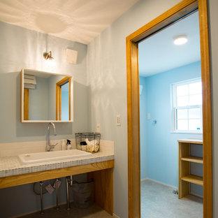 他の地域のカントリー風おしゃれなトイレ・洗面所 (青い壁、コンクリートの床、オーバーカウンターシンク、タイルの洗面台、グレーの床、青い洗面カウンター) の写真