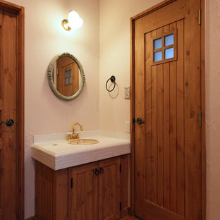 Design ideas for a scandinavian cloakroom in Other with medium wood cabinets, white walls, medium hardwood flooring, a built-in sink, tiled worktops and brown floors.