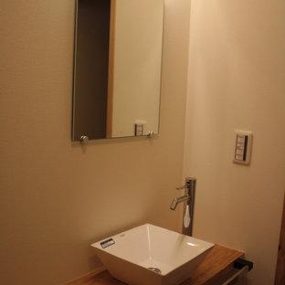 Cette image montre un WC et toilettes avec un sol en bois clair, un plan de toilette en bois, un plafond en bois et du papier peint.