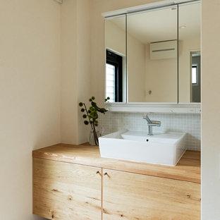 Diseño de aseo de estilo zen con armarios con paneles lisos, puertas de armario marrones, paredes blancas, lavabo sobreencimera, encimera de madera, suelo beige y encimeras marrones