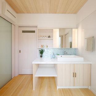 Aménagement d'un WC et toilettes contemporain de taille moyenne avec un placard à porte affleurante, des portes de placard beiges, un carrelage bleu, un carrelage en pâte de verre, un mur blanc, un sol en bois clair, une vasque, un plan de toilette en carrelage, un sol beige et un plan de toilette blanc.