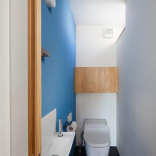 Kleine Moderne Gästetoilette mit flächenbündigen Schrankfronten, hellbraunen Holzschränken, Toilette mit Aufsatzspülkasten, Linoleum und schwarzem Boden in Yokohama