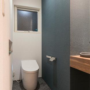 他の地域の中くらいのモダンスタイルのおしゃれなトイレ・洗面所 (オープンシェルフ、白いキャビネット、黒い壁、アンダーカウンター洗面器、緑の床、造り付け洗面台、クロスの天井、壁紙) の写真