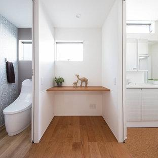 他の地域のモダンスタイルのおしゃれなトイレ・洗面所 (フラットパネル扉のキャビネット、白いキャビネット、一体型トイレ、白い壁、コルクフローリング、一体型シンク、茶色い床、白い洗面カウンター) の写真