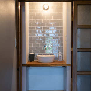 Mittelgroße Moderne Gästetoilette mit offenen Schränken, weißen Schränken, grauen Fliesen, Porzellanfliesen, weißer Wandfarbe, braunem Holzboden, Einbauwaschbecken, beigem Boden, beiger Waschtischplatte, eingebautem Waschtisch und freigelegten Dachbalken in Sonstige
