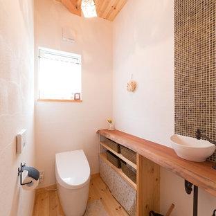 他の地域のアジアンスタイルのおしゃれなトイレ・洗面所 (オープンシェルフ、茶色いタイル、白い壁、淡色無垢フローリング、ベッセル式洗面器、木製洗面台、茶色い床、ブラウンの洗面カウンター) の写真