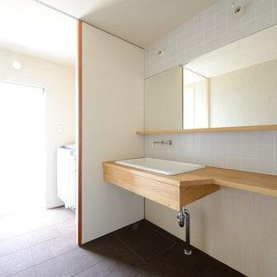 Idée de décoration pour un WC et toilettes minimaliste avec un carrelage noir, un sol en liège et un plan de toilette en bois.