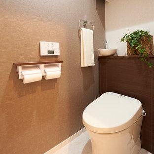 東京23区の中くらいのモダンスタイルのおしゃれなトイレ・洗面所 (一体型トイレ、茶色い壁、クッションフロア、白い床、クロスの天井、壁紙) の写真