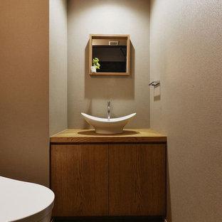 Asiatische Gästetoilette mit flächenbündigen Schrankfronten, hellbraunen Holzschränken, brauner Wandfarbe, Aufsatzwaschbecken, Waschtisch aus Holz, braunem Boden und brauner Waschtischplatte