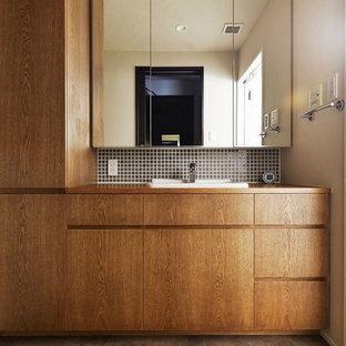 Modelo de aseo asiático con puertas de armario marrones, paredes blancas, lavabo encastrado, encimera de madera, suelo marrón y encimeras marrones