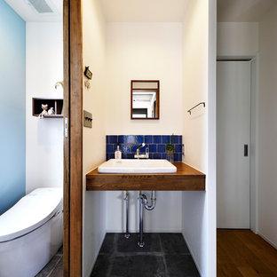 Inspiration pour un WC et toilettes urbain avec un carrelage bleu, un mur blanc, béton au sol, un plan vasque, un sol gris, un plan de toilette en bois et un plan de toilette marron.