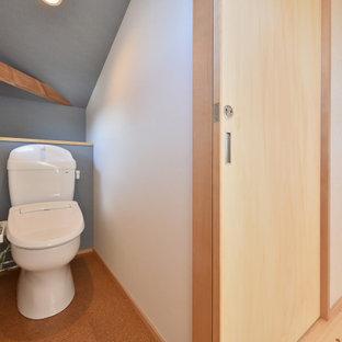 Aménagement d'un WC et toilettes avec des portes de placard blanches, un WC à poser, un carrelage vert, un sol en liège, un sol marron, un plafond en papier peint et du papier peint.