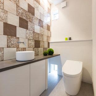 Diseño de aseo asiático con baldosas y/o azulejos marrones, paredes multicolor y suelo gris