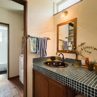 Idee per un bagno di servizio rustico con parquet scuro, top piastrellato, pavimento marrone e top blu