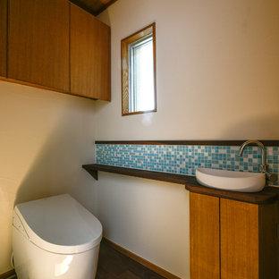 他の地域のアジアンスタイルのおしゃれなトイレ・洗面所 (フラットパネル扉のキャビネット、中間色木目調キャビネット、白い壁、濃色無垢フローリング、ベッセル式洗面器、木製洗面台、茶色い床) の写真