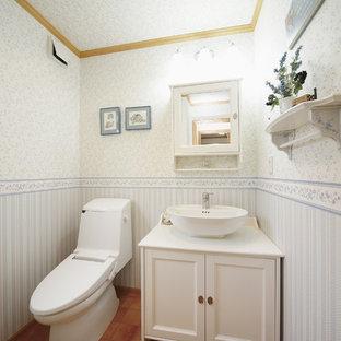 Стильный дизайн: туалет в классическом стиле с фасадами с утопленной филенкой, белыми фасадами, разноцветными стенами, полом из терракотовой плитки, настольной раковиной и оранжевым полом - последний тренд