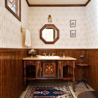 Новый формат декора квартиры: большой туалет в классическом стиле с фасадами островного типа, темными деревянными фасадами, раздельным унитазом, бежевыми стенами, полом из керамогранита, накладной раковиной, столешницей из оникса, розовым полом и оранжевой столешницей