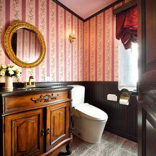 東京都下のシャビーシック調のおしゃれなトイレ・洗面所 (ヴィンテージ仕上げキャビネット、ピンクの壁、オーバーカウンターシンク、グレーの床) の写真