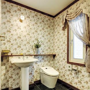 東京都下の広いトラディショナルスタイルのおしゃれなトイレ・洗面所 (一体型トイレ、白いタイル、白い壁、磁器タイルの床、ペデスタルシンク、テラゾーの洗面台、黒い床、白い洗面カウンター) の写真