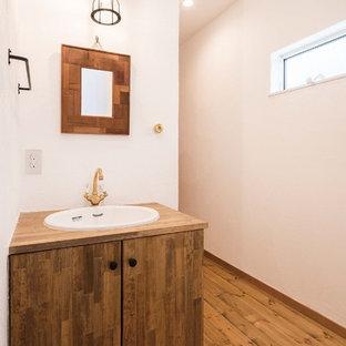 横浜の小さいインダストリアルスタイルのおしゃれなトイレ・洗面所 (フラットパネル扉のキャビネット、中間色木目調キャビネット、白い壁、無垢フローリング、オーバーカウンターシンク、木製洗面台、茶色い床、ブラウンの洗面カウンター) の写真