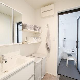 他の地域, のモダンスタイルのおしゃれなトイレ・洗面所 (フラットパネル扉のキャビネット、白いキャビネット、白い壁、一体型シンク、グレーの床) の写真