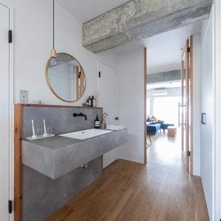 Kleine Moderne Gästetoilette mit offenen Schränken, grauen Schränken, weißer Wandfarbe, braunem Holzboden, integriertem Waschbecken, grauer Waschtischplatte, eingebautem Waschtisch, freigelegten Dachbalken und Tapetenwänden in Osaka