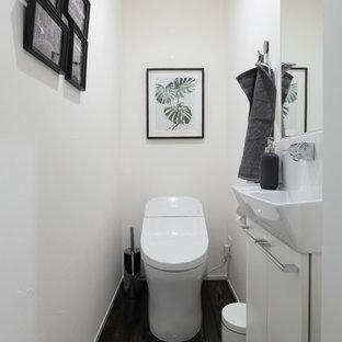 他の地域のモダンスタイルのおしゃれなトイレ・洗面所 (フラットパネル扉のキャビネット、白いキャビネット、一体型トイレ、白いタイル、白い壁、濃色無垢フローリング、壁付け型シンク、人工大理石カウンター、茶色い床、白い洗面カウンター) の写真