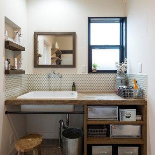 Cette photo montre un WC et toilettes industriel avec un placard sans porte, des portes de placard en bois vieilli, un mur blanc, un sol en bois peint, un lavabo posé, un plan de toilette en bois et un sol gris.