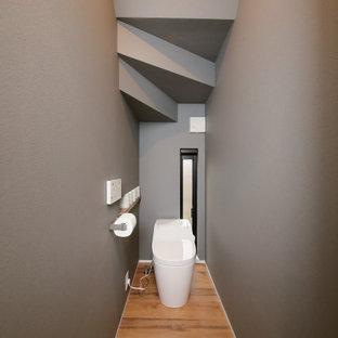 Inredning av ett industriellt mellanstort toalett, med en toalettstol med separat cisternkåpa, grå väggar, mörkt trägolv och brunt golv