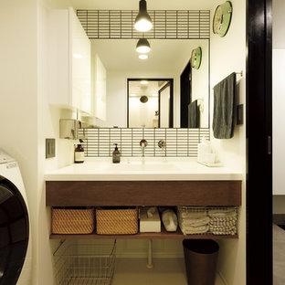 Cette photo montre un WC et toilettes asiatique avec un placard à porte plane, des portes de placard en bois sombre, un carrelage blanc, un mur blanc, un lavabo intégré, un sol beige et un plan de toilette blanc.