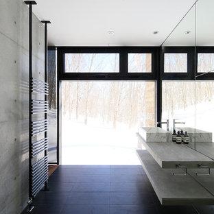 Idee per un bagno di servizio industriale con top in cemento, pavimento nero, nessun'anta, ante grigie, pareti grigie e lavabo a bacinella