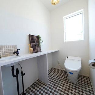 他の地域の北欧スタイルのおしゃれなトイレ・洗面所 (白い壁、オーバーカウンターシンク、マルチカラーの床) の写真