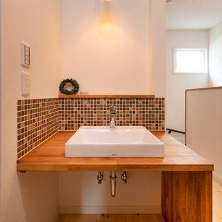 他の地域のラスティックスタイルのおしゃれなトイレ・洗面所 (茶色いタイル、白い壁、淡色無垢フローリング、ベッセル式洗面器、白い床、ブラウンの洗面カウンター) の写真
