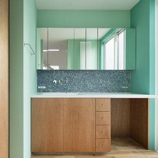 Aménagement de WC et toilettes modernes de taille moyenne avec un placard à porte plane, des portes de placard en bois brun, un carrelage vert, carrelage en mosaïque, un mur vert, un sol en bois brun, un lavabo encastré, un plan de toilette en surface solide et un sol beige.