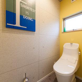 大阪のインダストリアルスタイルのおしゃれなトイレ・洗面所 (黄色い壁、グレーの床) の写真