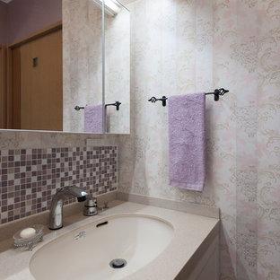 Идея дизайна: маленький туалет в стиле шебби-шик с фасадами островного типа, белыми фасадами, розовой плиткой, стеклянной плиткой, розовыми стенами, полом из винила, врезной раковиной, столешницей из искусственного камня и бежевым полом