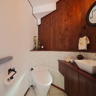 東京都下のミッドセンチュリースタイルのおしゃれなトイレ・洗面所 (フラットパネル扉のキャビネット、濃色木目調キャビネット、マルチカラーの壁、ベッセル式洗面器、木製洗面台、ベージュの床、ブラウンの洗面カウンター) の写真