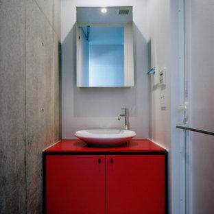 Стильный дизайн: маленький туалет в стиле модернизм с красными фасадами, серыми стенами, полом из винила, настольной раковиной, столешницей из искусственного камня, белым полом и красной столешницей - последний тренд
