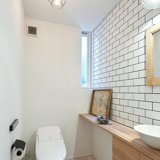 他の地域の小さいインダストリアルスタイルのおしゃれなトイレ・洗面所 (フラットパネル扉のキャビネット、淡色木目調キャビネット、白いタイル、サブウェイタイル、白い壁、クッションフロア、ベッセル式洗面器、木製洗面台、グレーの床、白い洗面カウンター) の写真