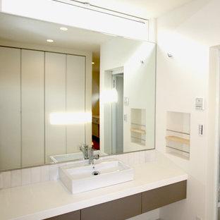 На фото: туалет в стиле модернизм с плоскими фасадами, серыми фасадами, белой плиткой, керамогранитной плиткой, белыми стенами, полом из ламината, настольной раковиной, столешницей из ламината и бежевым полом с