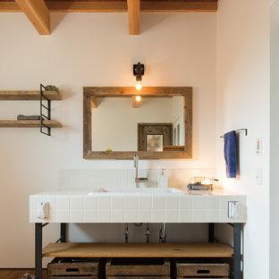 他の地域のインダストリアルスタイルのおしゃれなトイレ・洗面所 (オープンシェルフ、白いタイル、磁器タイル、タイルの洗面台、白い壁、無垢フローリング、オーバーカウンターシンク、茶色い床) の写真