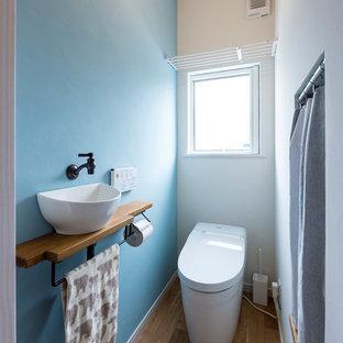 他の地域の小さい北欧スタイルのおしゃれなトイレ・洗面所 (青い壁、無垢フローリング、ベッセル式洗面器、木製洗面台、茶色い床、ブラウンの洗面カウンター) の写真