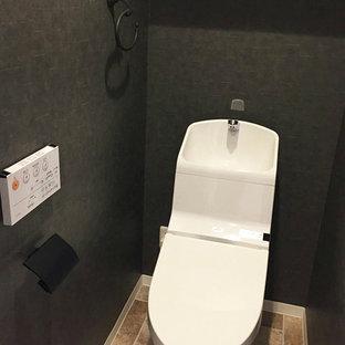 東京23区のラスティックスタイルのおしゃれなトイレ・洗面所 (一体型トイレ、黒い壁、ライムストーンの床、茶色い床) の写真