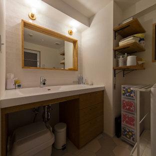 Inspiration pour un petit WC et toilettes minimaliste avec un placard à porte affleurante, des portes de placard marrons, un carrelage blanc, du carrelage en ardoise, un mur blanc, un lavabo intégré, un sol gris et un plan de toilette blanc.