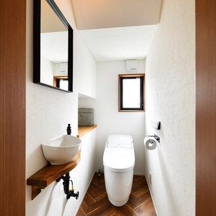 Ejemplo de aseo asiático, pequeño, con paredes blancas, suelo de madera oscura, lavabo sobreencimera y suelo marrón