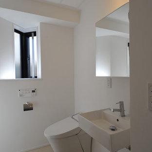 Ispirazione per un piccolo bagno di servizio contemporaneo con ante lisce, ante bianche, piastrelle bianche, pareti bianche, pavimento in linoleum, lavabo sospeso, top piastrellato, pavimento beige e top bianco
