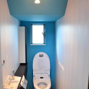 Ejemplo de aseo moderno con sanitario de una pieza, paredes azules, suelo de contrachapado y lavabo integrado