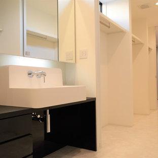 Cette photo montre un WC et toilettes moderne avec un placard à porte affleurante, des portes de placard noires, un carrelage blanc, un mur blanc, un sol en contreplaqué, un lavabo posé, un plan de toilette en surface solide, un sol blanc et un plan de toilette noir.