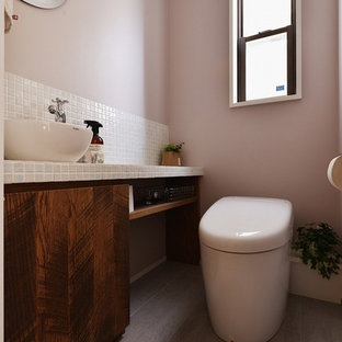 Неиссякаемый источник вдохновения для домашнего уюта: туалет в современном стиле с плоскими фасадами, фасадами цвета дерева среднего тона, розовыми стенами, настольной раковиной и серым полом